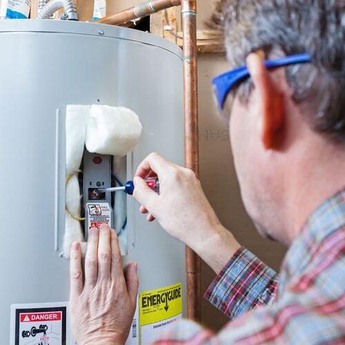 A Technician Repairs a Water Heater.