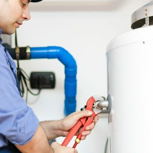 A Technician Repairs a Water Heater With a Wrench.